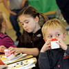 Manchester:  Charlie Swanson, 4, of Manchester finishes his milk as he listens to live jazz music at the annual Green and White Breakfast sponsored by the Manchester-Essex Rotary Club at the Manchester Essex High School cafeteria Saturday morning. Also pictured is Sophia Pomeroy, 8, and Paige Swanson, 7, left. Mary Muckenhoupt/Gloucester Daily Times