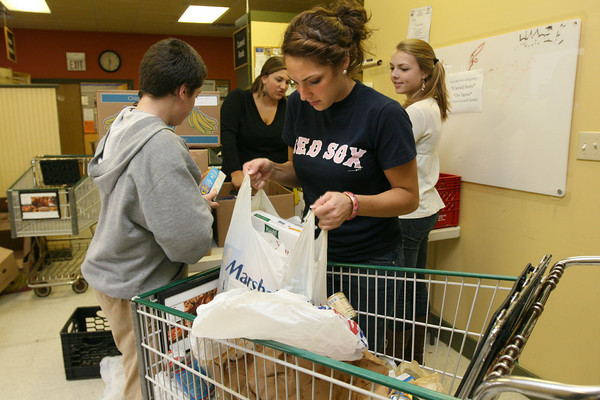 Gloucester: From left: Sean Kennedy, Mary Unis and Sabrina Parisi of the Gloucester High School Student Council and Megan Keegan of the Interact Club sort through shopping carts of items donated to the Open Door/Cape Ann Food Pantry yesterday morning. The organization will provide Thanksgiving dinners for 719 families. Photo by Kate Glass/Gloucester Daily Times Tuesday, November 24, 2009