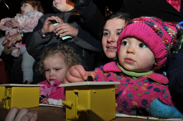 Gloucester: Christen Parsons and and her daughter Elliana 20 months (right) and 3 month old McKenzie Goulart push the switch to light the Xmass Tree at Kent Circle Sunday night. Desi Smith Photo/Gloucester Daily Times. November 29,2009.