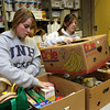 Gloucester: Meg Muniz and Brianna Aloisio of the Gloucester High School Student Council and Interact Club sort through shopping carts of items donated to the Open Door/Cape Ann Food Pantry yesterday morning. The organization will provide Thanksgiving dinners for 719 families. Photo by Kate Glass/Gloucester Daily Times Tuesday, November 24, 2009