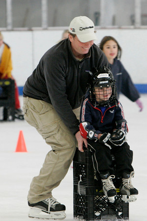 "Gloucester: Tucker Redinger, 4, of Gloucester gets a push from his dad, Tom, at the Harvest Hoesdown Skating Party at Dorothy Talbot Rink Saturday afternoon.  The Harvest Hoedown was sponsored by the Cape Ann Skating Club, which offers ""learn to skate programs"" for hockey and figure skaters year-round. Mary Muckenhoupt/Gloucester Daily times"