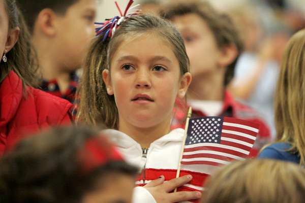 Gloucester: Taylor Abbott holds her hand over her heart for the Pledge of Allegiance while standing with the Plum Cover School Singers at the Veteran's Day Ceremony at Gloucester High School Wednesday morning. Mary Muckenhoupt/Gloucester Daily Times