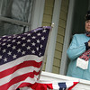 Gloucester: Phylis Curcuru stands on the porch of her Washington Street home to watch the Veteran's Day Ceremony in front of the American Legion Wednesday morning.  Curcuru's husband Nicholas served in World War II and her grandson Nicholas in currently serving in Iraq. Mary Muckenhoupt/Gloucester Daily Times