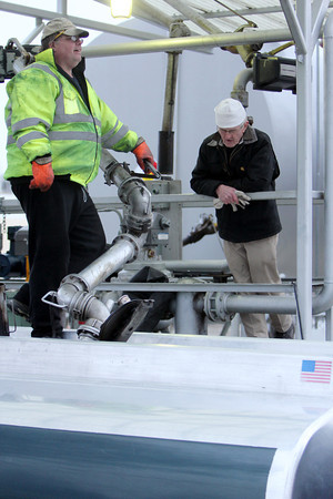 ALLEGRA BOVERMAN/Staff photo. Gloucester Daily Times. Gloucester: Dave Pierce, left, of Scott Energy Co., Inc. refills his delivery truck with home heating oil as coworker David Dow, right, chats with him. Both men are from Gloucester.
