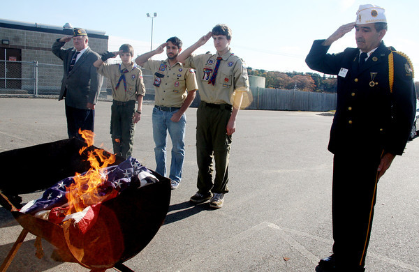 ALLEGRA BOVERMAN/Staff photo. Gloucester Daily Times. Manchester: The American Legion Post 113 held its Veterans Day ceremony at its headquarters on Friday morning and also held a flag burning ceremony to properly retire old, tattered flags. From left to right are Sgt.-at-Arms Charles Hunt, Troop 3 Boy Scouts Thomas Ambrose, Tyler Rossi and Alex Shepard, and Sgt.-at-Arms for the state commander.