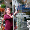 ALLEGRA BOVERMAN/Staff photo. Gloucester Daily Times. Gloucester: Gina Russo, co-owner of Sage Floral Studio, cleans the shop's windows on Tuesday afternoon.