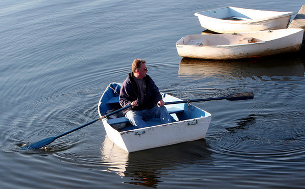 ALLEGRA BOVERMAN/Staff photo. Gloucester Daily Times. Manchester: Glenn Hoysradt of Gloucester takes his dinghy to his boat to do some maintenance on it at the town docks in Manchester on Wednesday afternoon.
