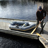 ALLEGRA BOVERMAN/Staff photo. Gloucester Daily Times. Manchester: Peter Morse of Essex disembarks from his inflatable dinghy after taking it out for a little joyride on Tuesday afternoon. It became a bit windy so he came back to shore. Then he deflated his dinghy, packed it up into a bag, and went on his way with it over his shoulder.