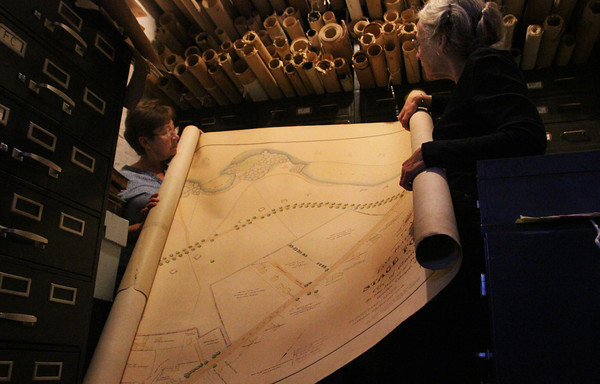 Janie Walsh, left, and Sarah Dunlap, co-chairs of the Gloucester Archives Committee, roll out a large 1898 planning map of what is now Stage Fort Park. The city has countless documents, all cramped into a few vults, much like this one. Jesse Poole/Gloucester Daily Time Nov. 7, 2011