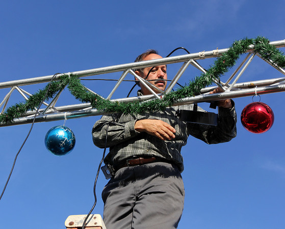 "Courtesy photo/Gloucester Daily Times. Gloucester: Brent ""Ringo"" Tarr sets up lights on the stage at Kent Circle where the Christmas Tree and parade festivities will take place on Sunday."