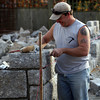 ALLEGRA BOVERMAN/Staff photo. Gloucester Daily Times. Rockport: Anthony Ciaramitaro, owner of Granite Design Stone Masonry of Gloucester, works on a 35-foot long wall he is building for a home along Granite Street in Rockport on Monday afternoon.