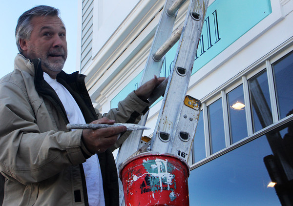 Carl Oulton, owner of Just Call the Guy, a local paint contraining company, says hello to a few passersby as he stands atop his ladder to touch-up-paint the exterior of Thistle Hill on Upper Main Street in Rockport. Jesse Poole/Gloucester Daily Times Nov. 4, 2011