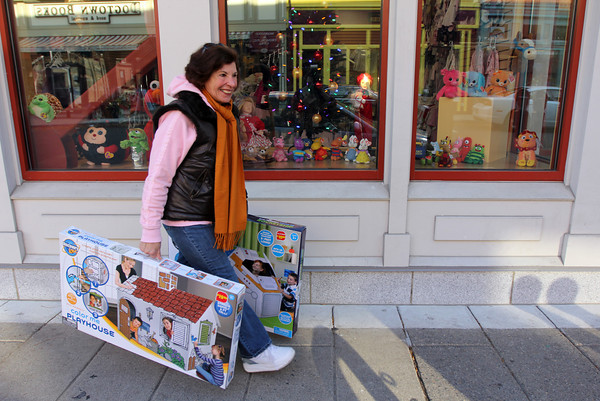 ALLEGRA BOVERMAN/Staff photo. Gloucester Daily Times. Gloucester: Mary Genovese, of Gloucster and Cape May, N.J., bought presents for her  grandchildren in downtown Gloucester on Friday morning and was walking home with them during the pleasant weather.