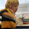 "Conner Burke, 5, practices number formation by using his finger to draw the number ""7"" in shaving cream with a few of his kindergarten classmates at Essex Elementary School on Tuesday afternoon. Jesse Poole/Gloucester Daily Times Nov. 1, 2011"