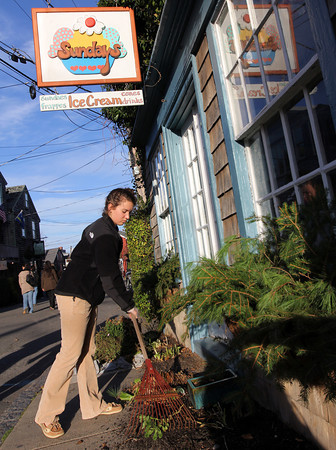 ALLEGRA BOVERMAN/Staff photo. Gloucester Daily Times. Rockport: Rhode Island resident Cori Sullivan, 16, visiting her grandmother Inge Sullivan, helps clean up the garden and grounds of the family's longtime ice cream shop, Sundays, in Bearskin Neck on Friday afternoon. The family was putting in greens for Christmas and other decorations, too. The shop is closed for the season.