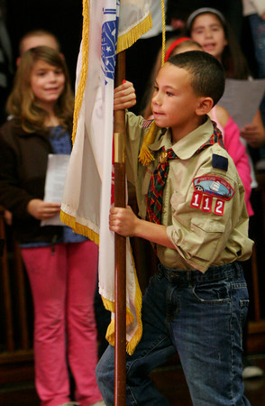 """ALLEGRA BOVERMAN/Staff photo. Gloucester Daily Times. Gloucester: Veterans Memorial School fourth grader Jared Mercado carries an Army flag during the singing of Salute to the Arms Services medley of songs during the  Veterans Day ceremony held at the school on Wednesday afternoon. He is a member of Boy Scout Troop 112. Students sang patriotic songs such as """"Bless Our Troops,"""" """"America the Beautiful,"""" and the Star Spangled Banner. A poem titled """"Veterans Day,"""" by Cheryl Dyson, was read by student Kayla Pennimpede."""