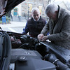 ALLEGRA BOVERMAN/Staff photo. Gloucester Daily Times. Rockport: Bob Smith, right, helps Phil Cutter on Tuesday afternoon with fixing the hose to his car's radiator. It apparently blew off while Cutter was driving. The two men are from Rockport.