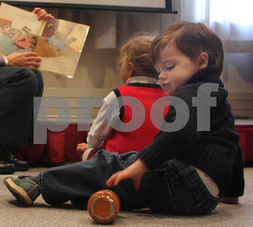 Reed Herlihy, 2, of Rockport, reaches for his bottle as a book about a family of raccoons is read aloud during the Preschool Story Hour at the Rockport Public Library on Tuesday morning. Jesse Poole/Gloucester Daily Times Nov. 1, 2011