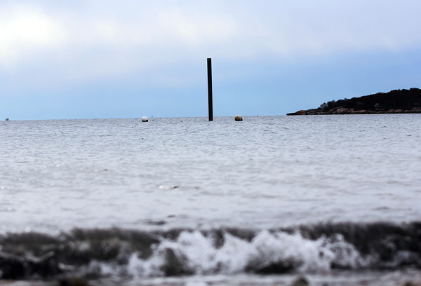 A lone pole protrudes from the water off Pavillion Beach and the Boulevard. This pole is the first piling in the construction of the new greasy pole structure. Jesse Poole/Gloucester Daily Times Nov. 17, 2011