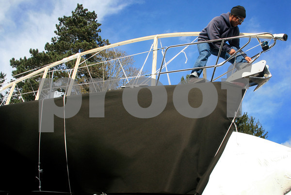 "ALLEGRA BOVERMAN/Staff photo. Gloucester Daily Times. Manchester: Mike Poirier of Gloucester, a Manchester Marine employee, is preparing this 28-foot boat named ""Allegro,"" for winterizing. The wooden framework has been place on top of it and it will be shrinkwrapped on Wednesday."