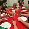 ALLEGRA BOVERMAN/Staff photo. Gloucester Daily Times. Gloucester: Thanksgiving is for turkey and football. Serving, at center, is Manchester Essex's Joe Burgess, seated around the table from far right, are Gloucester's Nick Taormina, Manchester Essex's Paul Pennoyer, from lower left to right are Cooper Riehl, Gloucester's Kyle Lucido and Manchester Essex's Mavrick MacEachearn.