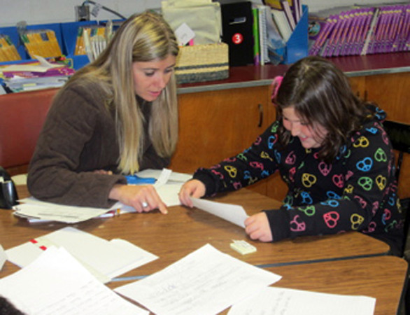 Courtesy Photo. Gloucester Daily Times. Gloucester: Mrs. Kailey Mione, a third grade teacher at Veterans' Memorial Elementary School, working with her student, Mikayla Beagal as she writes a draft of a Thanksgiving poem recently.