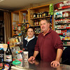 Brett Clayton, owner of the Lanesville Package Store, and store manager Julie Wentworth stand behind the store's counter together on Monday around noon. Jesse Poole/Gloucester Daily Times Nov. 14, 2011