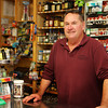 Brett Clayton, owner of the Lanesville Package Store, stands behind the counter he's been at for eight years now. Jesse Poole/Gloucester Daily Times Nov. 14, 2011