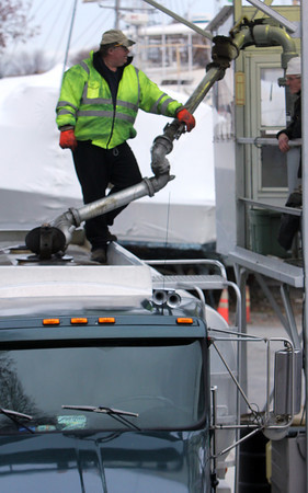 ALLEGRA BOVERMAN/Staff photo. Gloucester Daily Times. Gloucester: Dave Pierce of Scott Energy Co., Inc., left, refills his delivery truck with home heating oil as he talks with coworker David Dow, right on Tuesday afternoon. Both men are from Gloucester.