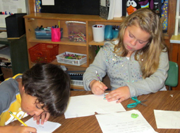 Courtesy Photo. Gloucester Daily Times. Gloucester: From left, Veterans Memorial Elementary School third graders Joshua Montesino and Talia Pata write Thanksgiving poems recently. Both are students in Mrs. Kailey Mione's third grade class.<br /> <br /> friendly competition studying
