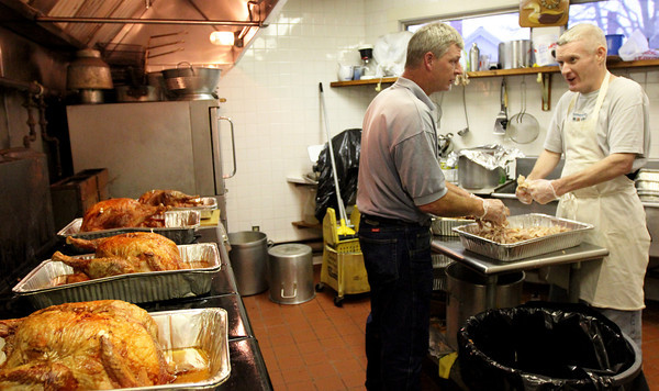 ALLEGRA BOVERMAN/Staff photo. Gloucester Daily Times. Gloucester: John Pasierbiak, left, and Matt Dow, both American Legion members and volunteers, have been busy preparing lots of turkeys in advance of Thanksgiving on Wednesday afternoon. By 3 p.m. they had made 15 turkeys, each weighing about 22 pounds. The American Legion hosts an annual dinner on Thanksgiving which is free and open to the public at their hall on Washington Street, and pack up and deliver hundreds of full meals to people in the area.
