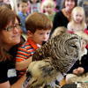 Max, a student of Tara Montessori School in Manchester, performs his hushed version of the hoot of a Barred Owl into a microphone for the children and adults at Manchester Community Center who've gathered to see Mark Wilson of Eyes on Owls showcase the birds. Jesse Poole/Gloucester Dialy Times Nov. 3, 2011