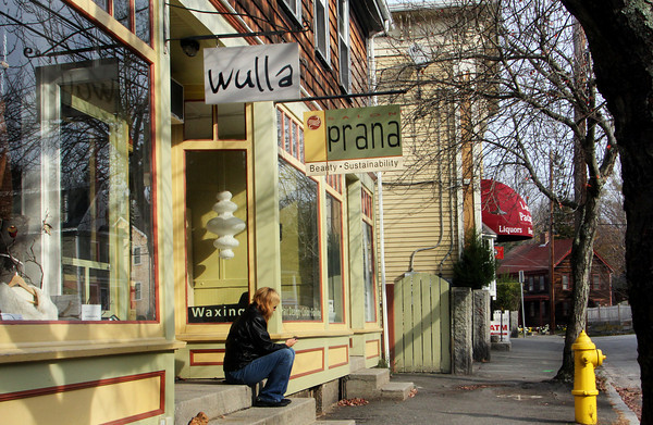 Florence Williams sits on the shared enterence steps of Wulla and Prana, waiting for her friend to come around the bend, passing the Package Store, to pick her up. These stores are three of a short row of Lanesville shops along Washington Street. Jesse Poole/Gloucester Daily Times Nov. 14, 2011