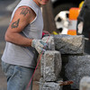 ALLEGRA BOVERMAN/Staff photo. Gloucester Daily Times. Rockport: Anthony Ciaramitaro, owner of Granite Design Stone Masonry of Gloucester, works on a 35-foot-long granite wall he is building along Granite Street in Rockport on Monday afternoon.