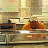 ALLEGRA BOVERMAN/Staff photo. Gloucester Daily Times. Gloucester: Jeff DiMeo. an Intershell Fish Market employee, at the counter. Lobster prices are above him on the board.