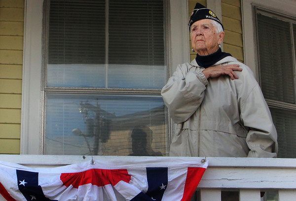 """Phyllis Curcuru, nearly 89, a veteran member of the American Legion, stands on her porch facing the Legion as the parade ends and folks gather at the Joan of Arc statue on Friday morning. Curcuru lost her husband, Nicholas, a WWII veteran, a month ago yesterday. """"He was a good man, a good, good man,"""" she said of her late husband on Friday. Nicholas Curcuru, Navy veteran, was deployed to New Guinea and Borneo from 1941 to 1945 and worked on PT rescue boats. Jesse Poole/Gloucester Daily Times Nov. 11, 2011"""