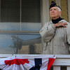 "Phyllis Curcuru, nearly 89, a veteran member of the American Legion, stands on her porch facing the Legion as the parade ends and folks gather at the Joan of Arc statue on Friday morning. Curcuru lost her husband, Nicholas, a WWII veteran, a month ago yesterday. ""He was a good man, a good, good man,"" she said of her late husband on Friday. Nicholas Curcuru, Navy veteran, was deployed to New Guinea and Borneo from 1941 to 1945 and worked on PT rescue boats. Jesse Poole/Gloucester Daily Times Nov. 11, 2011"