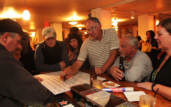 Larry Ingersoll gathers with his friends and family at Giuseppe's Ristorante while calculating the votes on Tuesday evening. Jesse Poole/Gloucester Daily Times Nov. 8, 2011