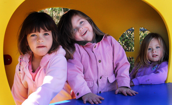"""From left, preschoolers Caroline Lucas, Cassandra Vincent and Morgan Sullivan enjoy the shade of their pretend ice cream stand in the playground of Rockport Elementary School on Wednesday morning. """"Ice cream, get your ice cream,"""" they yelled to their teachers and fellow preschoolers. Jesse Poole/Gloucester Daily Times Nov. 9, 2011"""