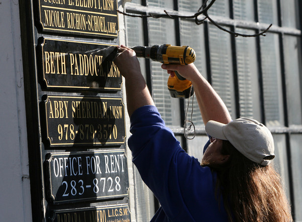 ALLEGRA BOVERMAN/Staff photo. Gloucester Daily Times. Gloucester:  Cheryl Newman-Lahti of West Gloucester, of Cheryl's Signs, installs a new sign for a new business at 19 Pleasant Street on Friday.