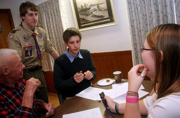 "ALLEGRA BOVERMAN/Staff photo. Gloucester Daily Times. Manchester: Alex Shepard, standing, of Manchester, is working on his  Eagle Scout Project titled ""Remembering Our Veterans."" He started interviewing local WWII and other veterans on Veterans Day at the American Legion Post 113 in Manchester. Seated, clockwise from left, is veteran Bob White, Calvin Lamothe, and Alyssa Shepard."