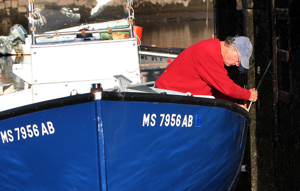 ALLEGRA BOVERMAN/Staff photo. Gloucester Daily Times. Manchester: Jim Groves unties his boat from a mooring at the town docks in Manchester on Wednesday afternoon.