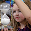 """Allegra Boverman/Gloucestert Daily Times. West Parish student Emily-Rose Lane examines a sand clock during """"The Big Fat Science Show"""" held at his school on Wednesday. The show, which is visiting all the elementary schools in Gloucester, features great inventions through the ages, from arrowheads to chain mail, motors to quill pens, maps to sextants."""