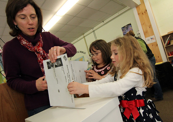 ALLEGRA BOVERMAN/Staff photo. Gloucester Daily Times. Students at Memorial Elementary School in Manchester were participating in a mock Election Day on Friday. First graders Amelia Costa, right, and Taylor Palmer, center, cast their ballots with the help of parent volunteer Melanie Oldeman.