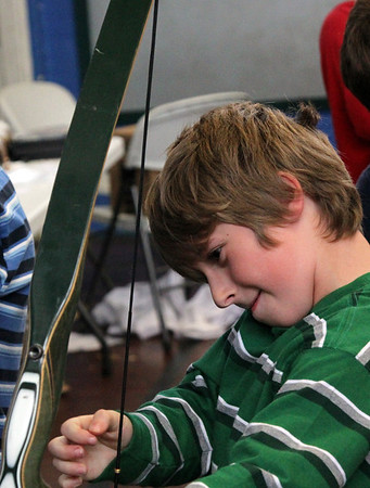 """Allegra Boverman/Gloucestert Daily Times. West Parish student Marcus Martin tries out a bow during """"The Big Fat Science Show"""" held at his school on Wednesday. The show, which features great inventions over the ages, is  visiting all the elementary schools in Gloucester."""