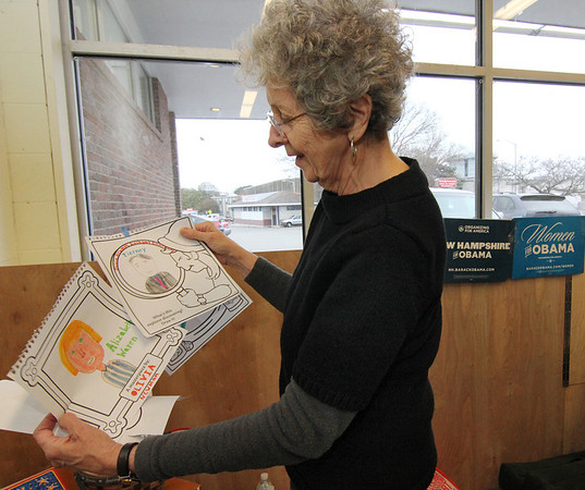 Allegra Boverman/Gloucester Daily Times. Helen Wiseman, chair of the Gloucester  Democratic Committee, looks at drawings of the Democratic candidates such as Elizabeth Warren and John Tierney done by children who visited the headquarters during the campaigns. She is dismantling the headquarters in downtown Gloucester now that the elections are over.