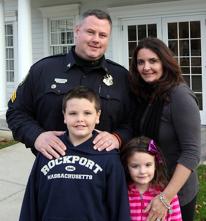 ALLEGRA BOVERMAN/Staff photo. Gloucester Daily Times. Rockport Sgt. Michael Marino helped save a choking woman on Sunday afternoon. He is surrounded by his wife, Danielle, daughter Grace, 5, and son Sam, 8.
