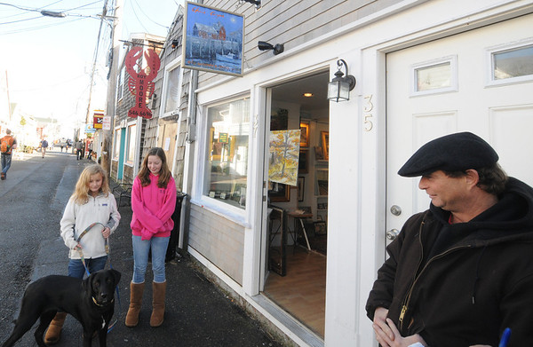 JIm Vaiknoras/Gloucester Daily Times. Chris Coyne talks about Black Friday at his gallery on Bearskin Neck in Rockport along with his daughters Kate , Clare and their dog Saphire.