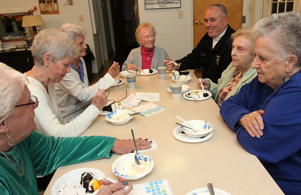 Allegra Boverman/Gloucester Daily Times. Evelyn Hickey, center back, was celebrating her 90th birthday this week - her birthday was on Tuesday. Essex Police Chief Peter Silva heard about her birthday and that she had no big plans for it, so he got a huge cake for her, in addition to learning other people at Chebacco Terrace, where she lives, were also celebrating birthdays in November. They held a birthday party with cake and ice cream on Thursday evening there. Seated around the table, from lower left are: Nancy Beattie, Fay Platt,  who both have November birthdays, Betty Smith, Hickey, Chief Silva, Gloria Story and Lois Kleindienst, whose birthday was in October. Also celebrating a birthday but not in the photo: Peter Landry and Janice Farnham.
