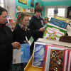 JIm Vaiknoras/Gloucester Daily Times. Lisa White looks for a book for her grandson Matthew in The Book Store in Gloucester with her children Molly 14, and Zack 15.